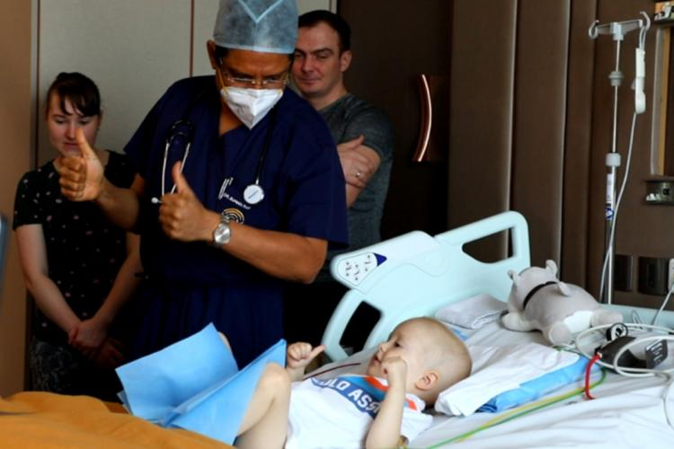 Lev Fedorenk showing thumps up along with a doctor during the recovery process. His mom and dad are also present in the image