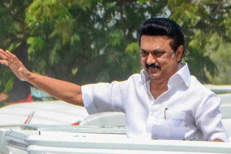 MK Stalin waving to the crowd from a van
