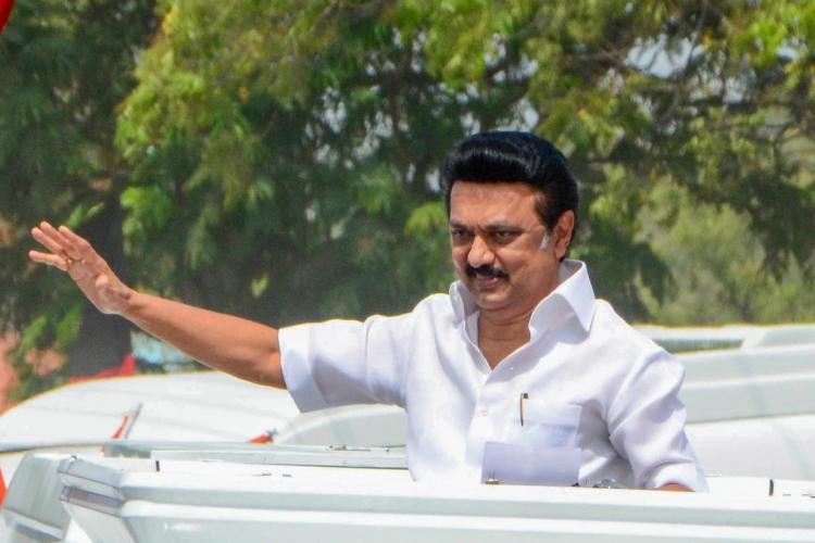 MK Stalin in white shirt seen from waist up standing and waving