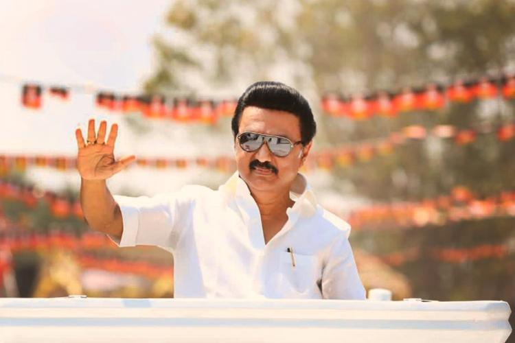 DMKs MK Stalin wears sunglasses and waves to a crowd during a poll campaign from the sunroof of his vehicle with dmk flags behind him