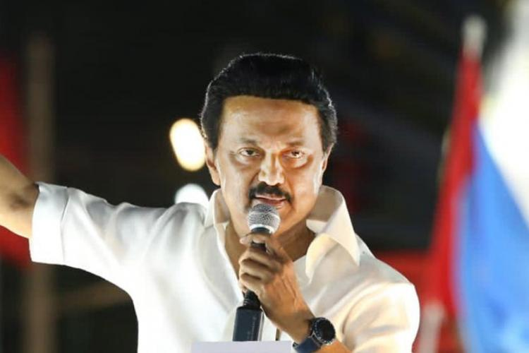 MK Stalin holds a mic and gesticulates during a campaign rally