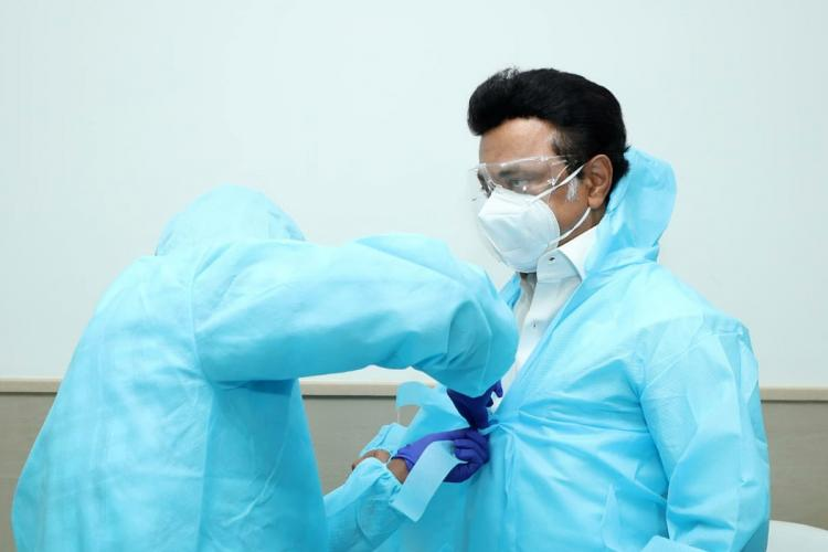 Tamil Nadu CM MK Stalin being helped by a man to wear a PPE kit