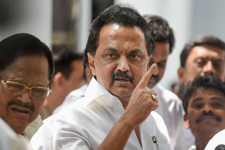 MK Stalin addressing the press surrounded by cadre and raising his hand and pointing a finger