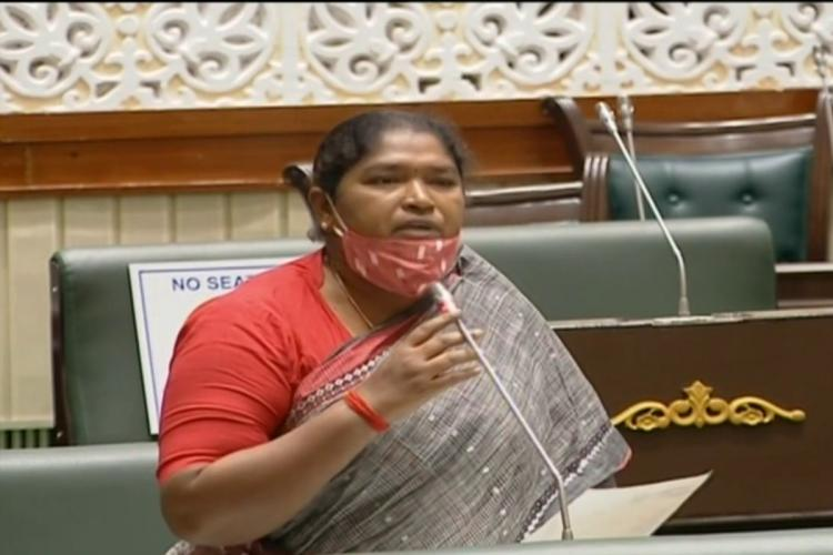 MLA Seethakka in a grey and red saree in the Telangana Assembly wearing a red mask and speaking into a mic