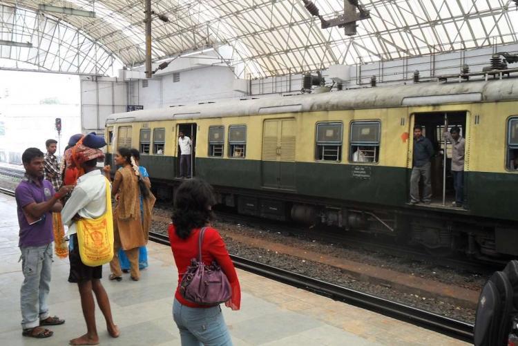 Suburban train in Chennai with passenger waiting outside