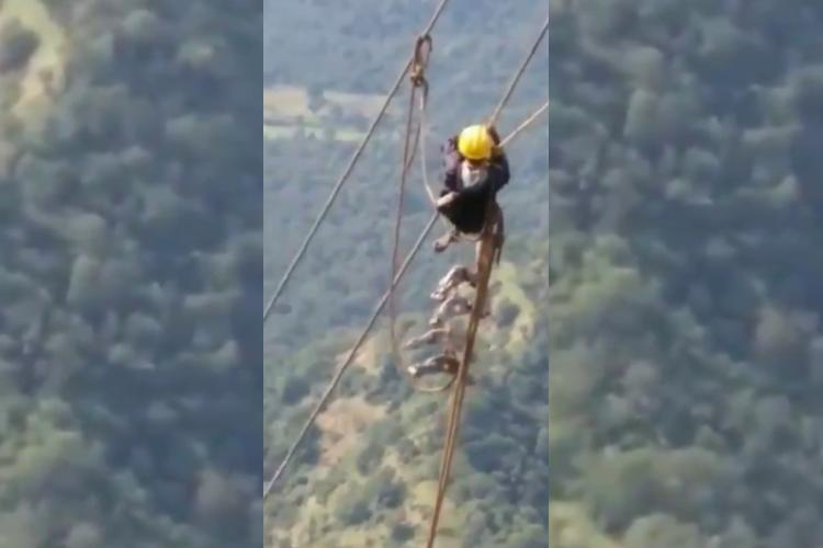 Maharashtra State Electricity Board employee hanging from a wire in the mountains in Khandala