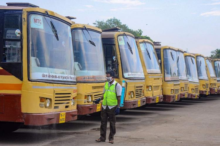 A fleet of MTC buses being disinfected during COVID pandemic by a worker