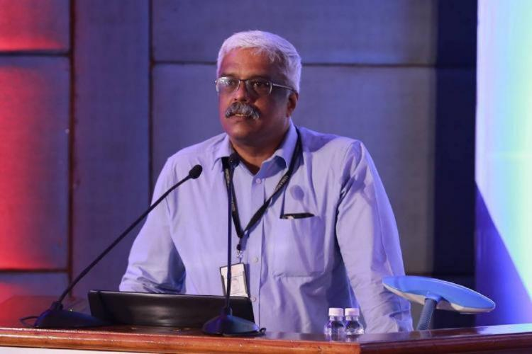 Sivasankar at a podium speaks before a microphone wearing a light blue shirt and a tag