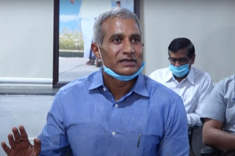 Andhra Pradesh Bureaucrat Madireddy Pratap in a blue shirt and mask looking to his left and speaking with his right hand slightly raised at a press meet