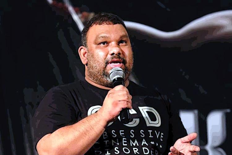 Kathi Mahesh, in a black T shirt, addressing a gathering