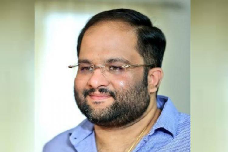 Producer Mahesh Koneru in a blue shirt wearing spectacles