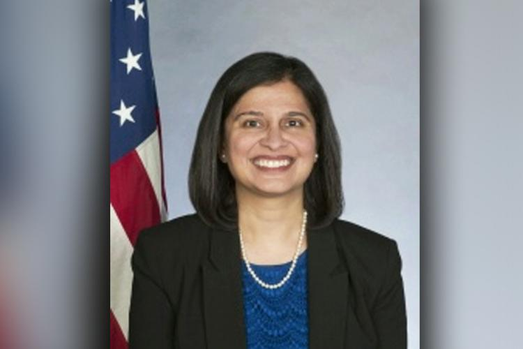 Mala Adiga in a black blazer worn over a blue outfit posing with the US flag behind her She is smiling directly at the camera