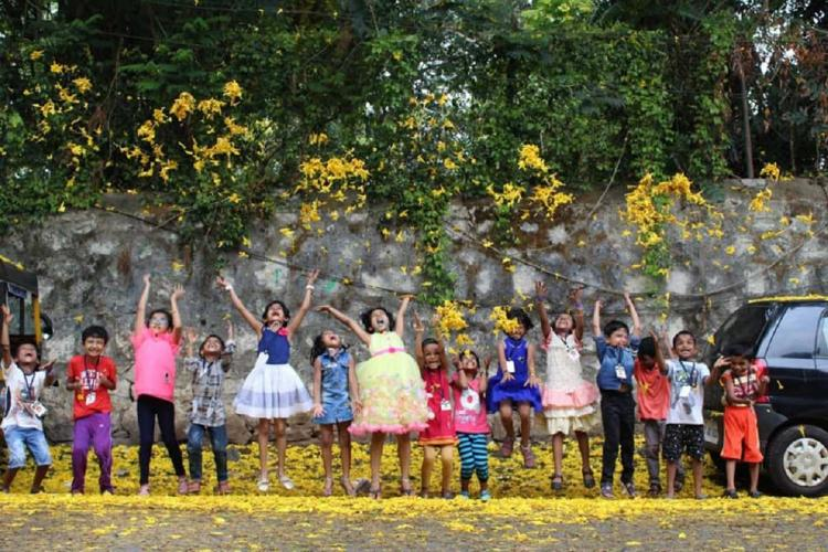 A bunch of little children standing next to each other jump up in this photo below them are yellow flowers fallen from a tree above
