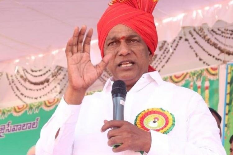 Ch Malla Redd wearing an orange hat and addressing public