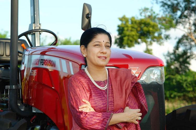 Chairman and Managing Director of TAFE Mallika Srinivasan in a dark pink kurta leaning against a tractor with her arms folded