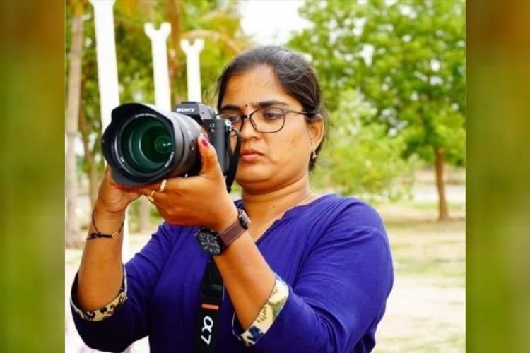 Mallishwari in an event as a camera woman holding camera by wearing a blue top