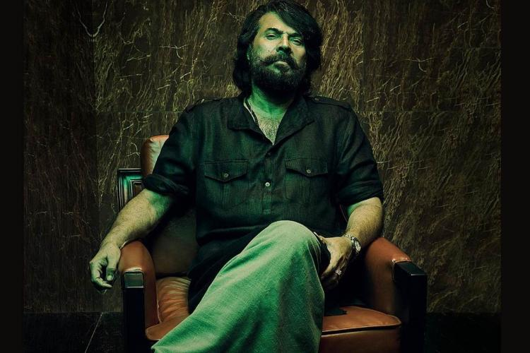 Mammootty wearing a dark shirt and pants has long hair a beard and sits on a chair against a brown background