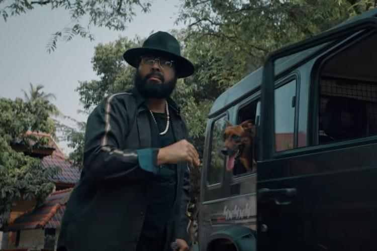 Mammootty in black robes and a hat and long bears is near a car and a dog is inside it