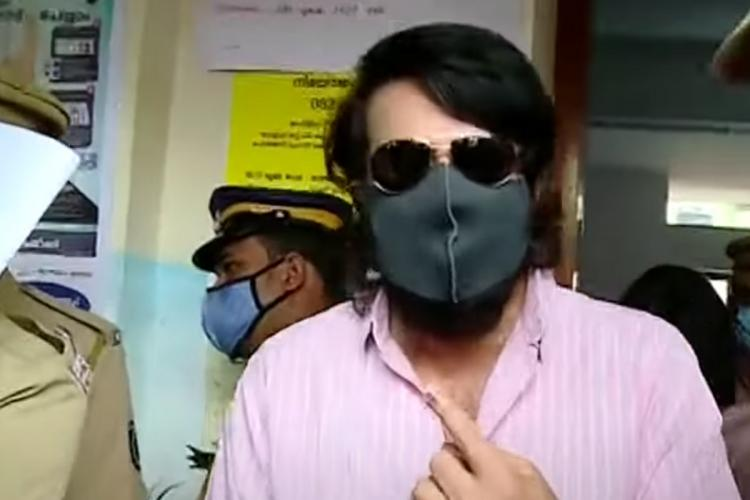 Mammootty shows his inked finger after casting his vote in Kochi on Tuesday He is wearing a pink shirt mask