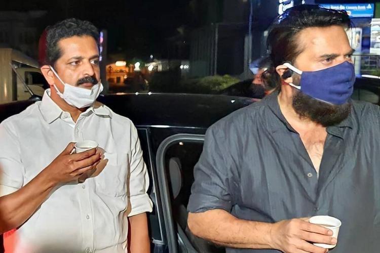 Man in white and Mammootty in grey have tea in paper cups wearing their masks