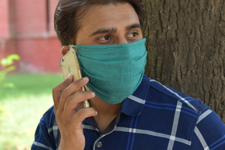 Man in a blue shirt wearing a mask talking on the phone