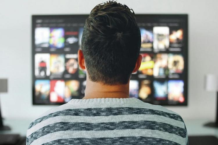 A man is looking at a TV screen and streaming videos on OTT platform