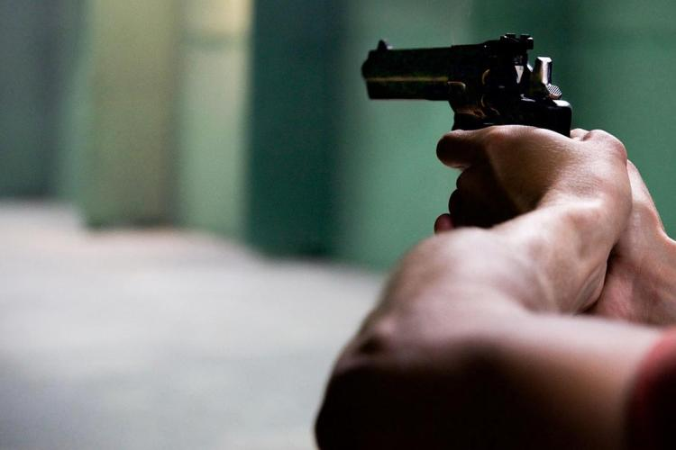 Man holding a gun and aiming at an unseen victim