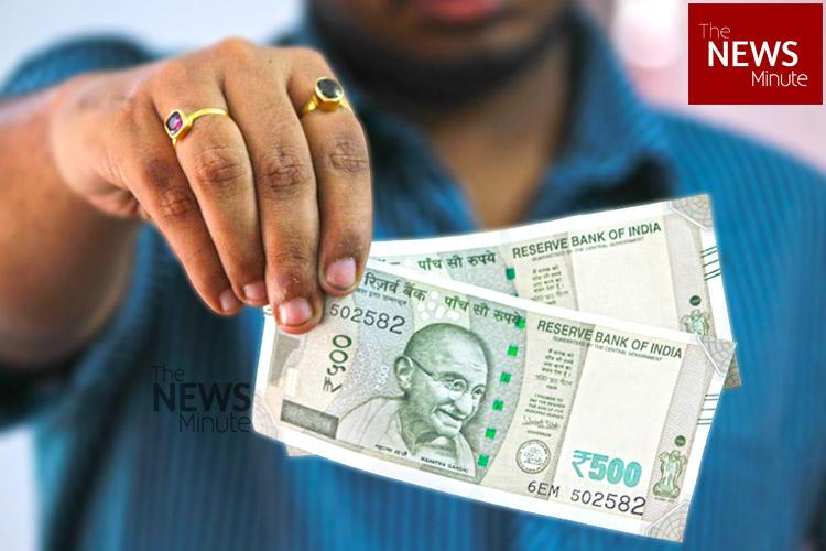 Man in blue shirt holding five hundred rupees notes