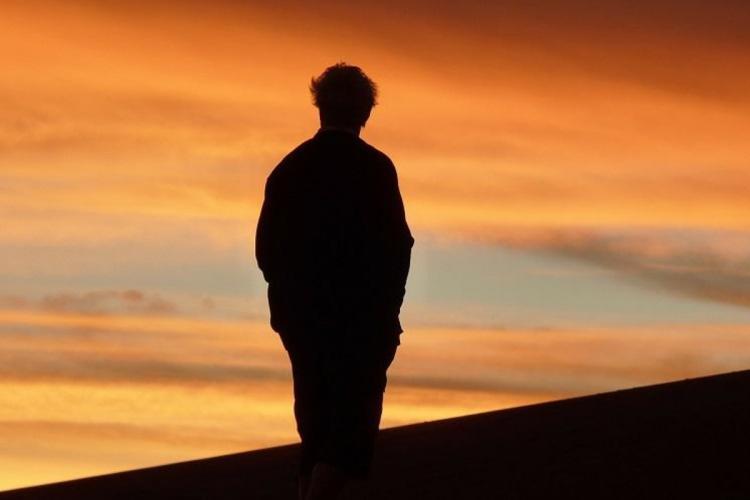 Silhouette of a man against an orange sky