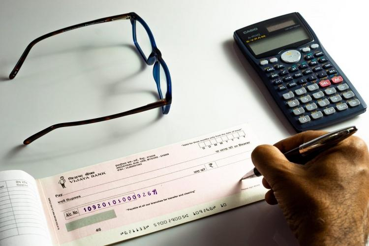 A man writing on a Vijaya Bank cheque with specs and a scientific calculator in the background
