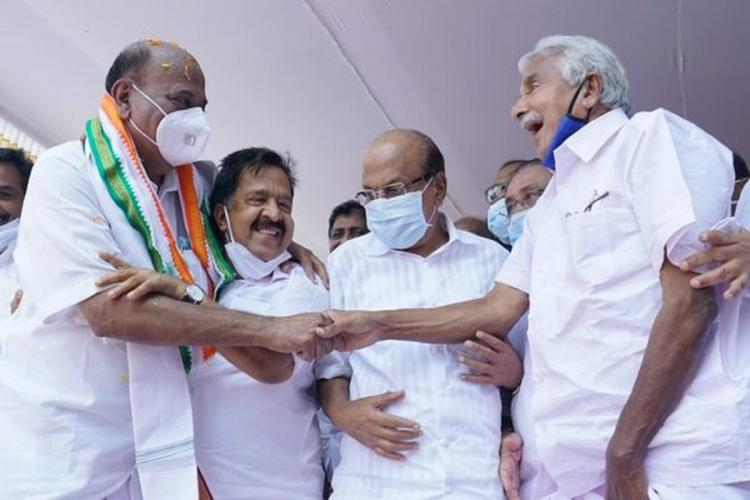 Mani C Kappen and Oommen Chandy shake hands Ramesh Chennithala and PK Kunhalikutty are also on stage The UDF leaders are sharing a light moment