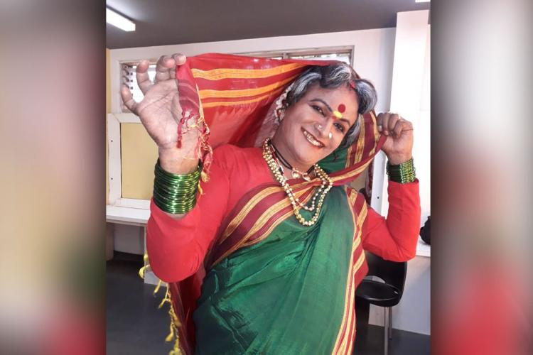 Manjamma Jogathi the first transgender person to head the Karnataka Janapada Academy in a green saree with a red border and red blouse She has the saree pallu over her head and poses with a wide smile