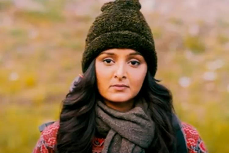 Manju Warrier in a monkey cap with her hair let lose on either side and a grey muffler around her neck
