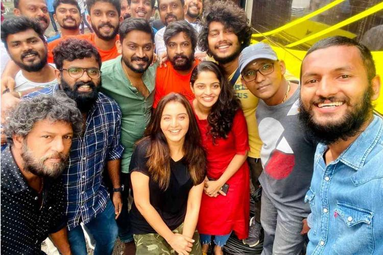 Manju Warrier poses in a black top with a group of 10-15 people from the Malayalam movie The Priest team