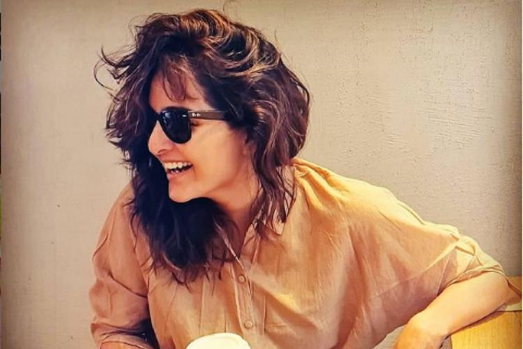 Manju Warrier in a lose yellow shirt looks sideways and laughs, has sunglasses, and her hair is swept to one side