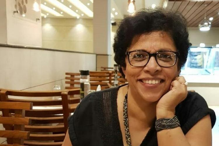 Manna in a black top bracelet and chain of beads around her neck is wearing a specs has cropped hair and smiles sitting at a restaurant