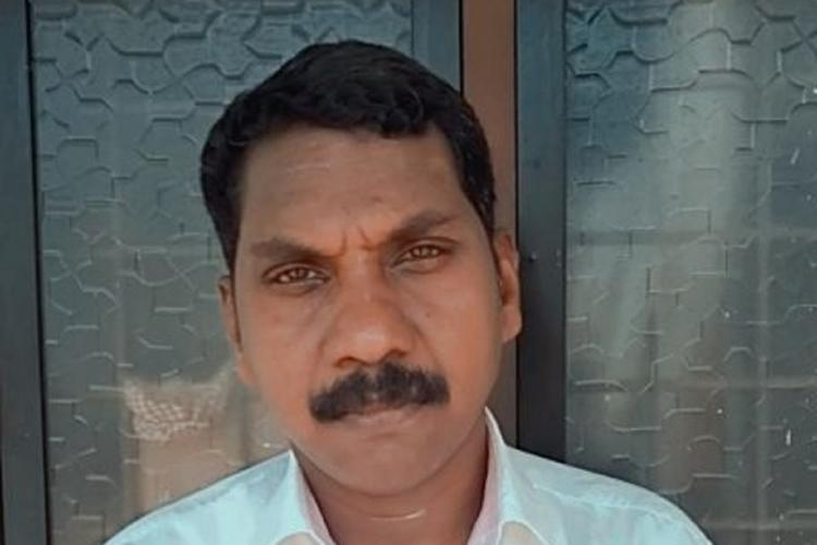 Manoharan wearing a light colour shirt has black hair and moustache and stands against a thick-glassed window