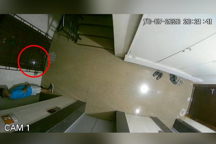 A CCTV footage of a man urinating near the grill gate of the house