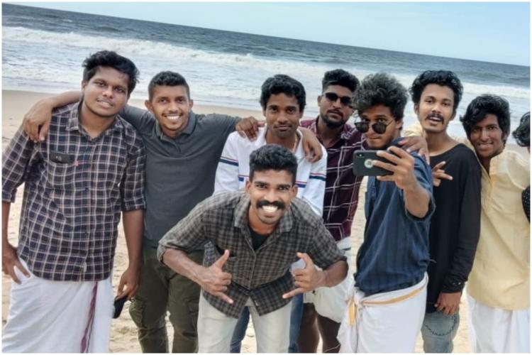 Kerala youth Manu Napolean with his friends on a beach.
