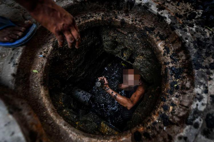 Worker engaged to clean manhole in India