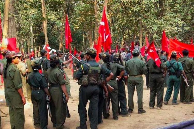 Maoists holding flags standing in line at an undisclosed location