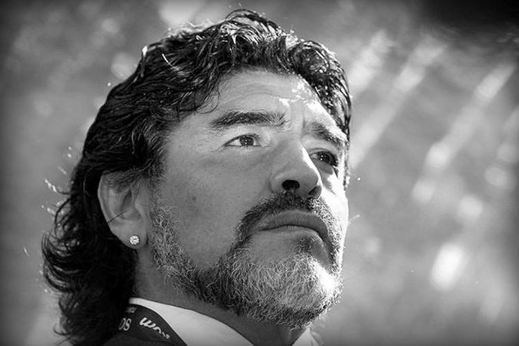 A black and white picture of Maradona. The footballl legend is seen looking up