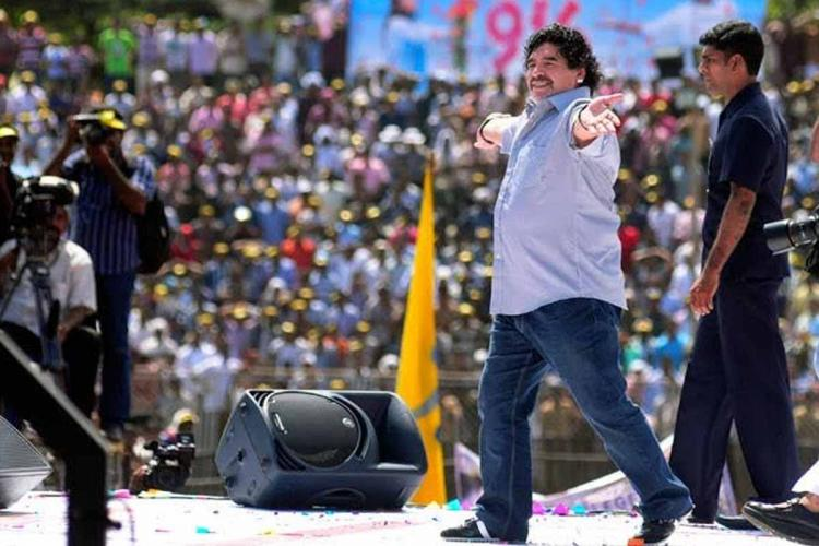 Maradona at a stadium in Kannur in Kerala in 2012 He is spreading out his hands and cheering audience who can be seen in the background