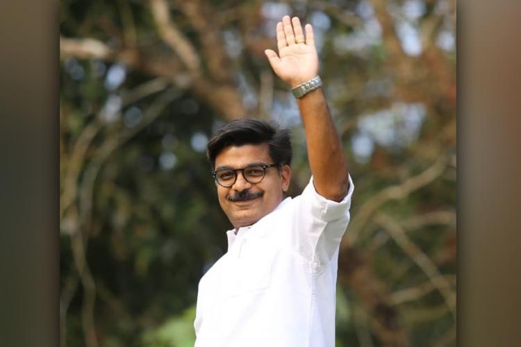 Congress candidate Mathew Kuzhalnadan wearing a white shirt is seen waving