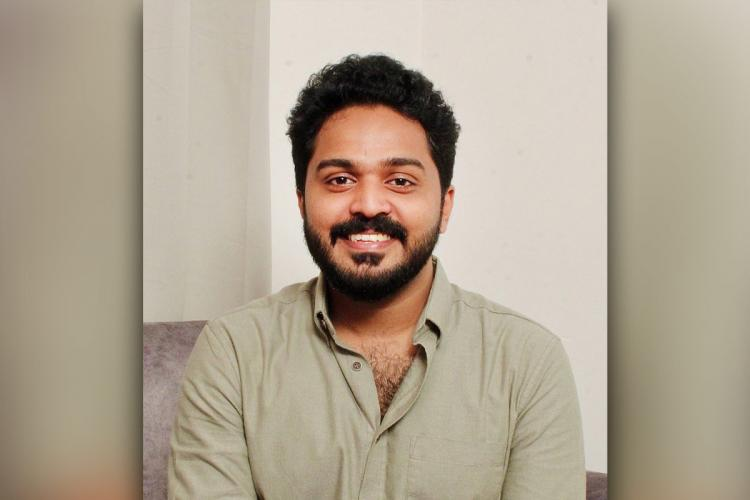 Mathukutty in a grey shirt smiles, has a beard and the background is white and grey