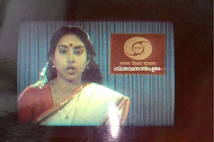A television screen in which Maya Sreekumar in white Kerala Sari and reed blouse reads the news on the right is Doordarshan icon and in the back a grey curtain