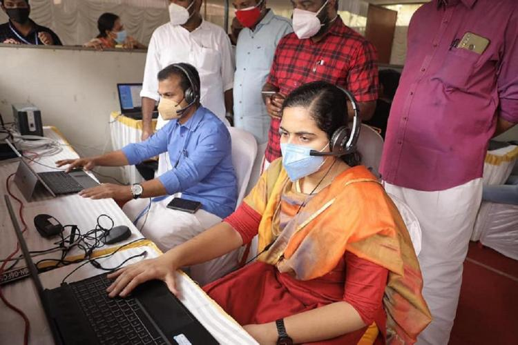 Arya and Prasanth sit before laptops wearing masks as four other men watch from behind