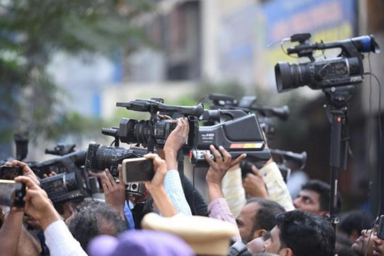 A group of media persons hold holding up cameras and mics