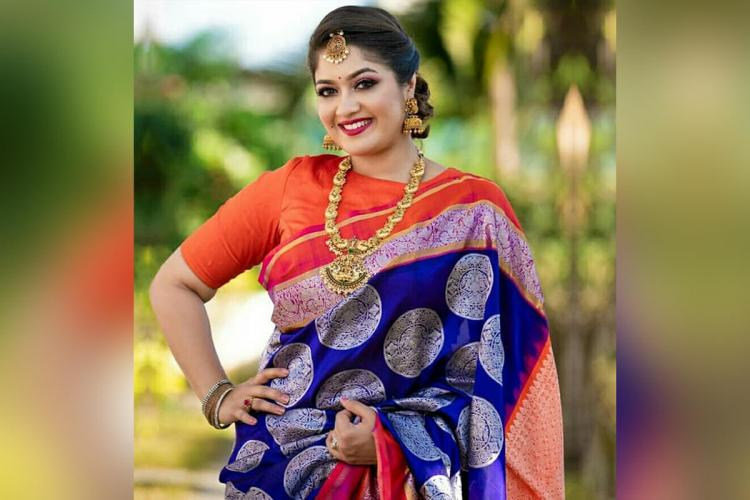 Actor Meghana Raj wearing a blue saree and orange blouse She is posing with her right hand on her hip