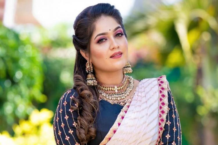 Meghana is seen in a white and blue designer saree sporting an ethnic look